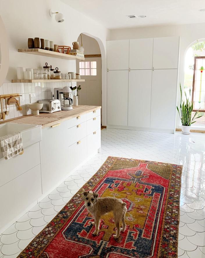 """<div class=""""caption""""> The vintage rug was a great way to add a big dose of color to the <a href=""""https://www.architecturaldigest.com/story/this-all-white-apartment-is-anything-but-monotonous?mbid=synd_yahoo_rss"""" rel=""""nofollow noopener"""" target=""""_blank"""" data-ylk=""""slk:bright, white space"""" class=""""link rapid-noclick-resp"""">bright, white space</a>. </div>"""