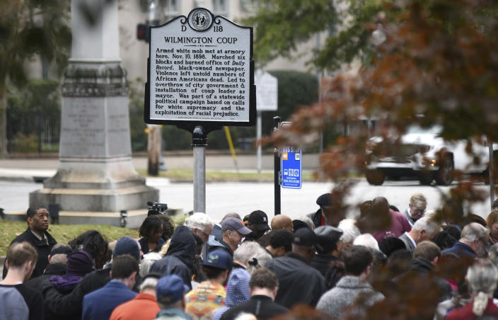 People stand under the new North Carolina highway historical marker to the 1898 Wilmington Coup during a dedication ceremony in Wilmington, N.C., Friday, Nov. 8, 2019. The marker stands outside the Wilmington Light Infantry building, the location where in 1898, white Democrats violently overthrew the fusion government of legitimately elected blacks and white Republicans in Wilmington. (Matt Born/The Star-News via AP)