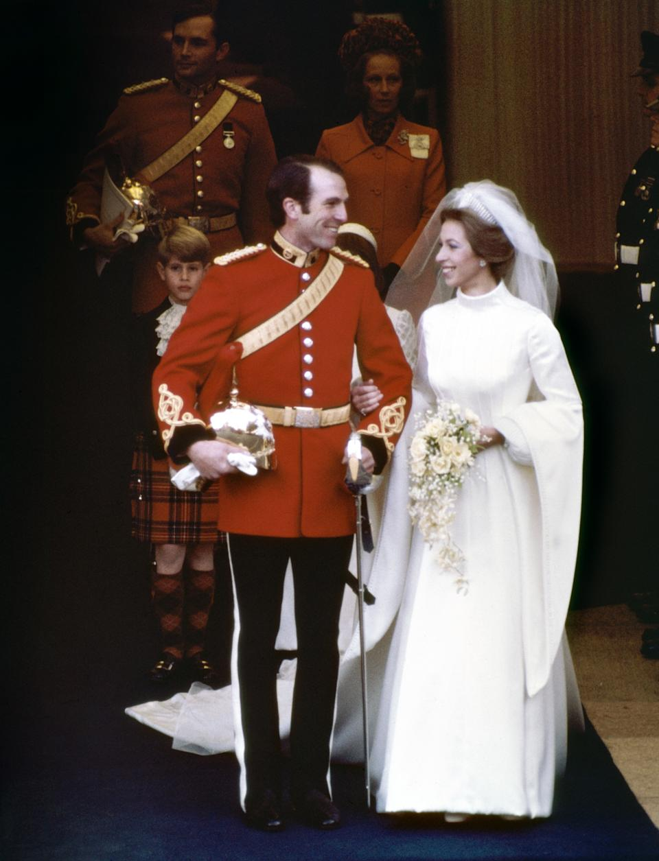 Princess Anne gave off '70s vibes with her first wedding dress as she married Captain Mark Phillips in a high-neck, wide-sleeved white dress in 1973.