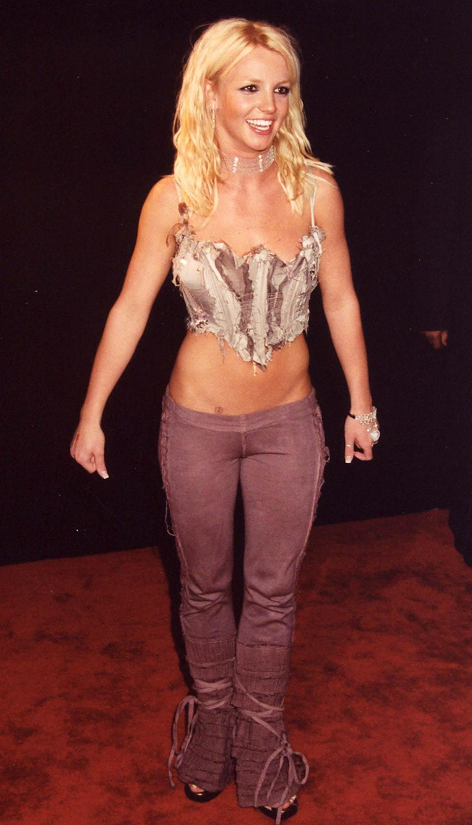 <p>Wearing low-rise pants with a barely-there top at an event.</p>