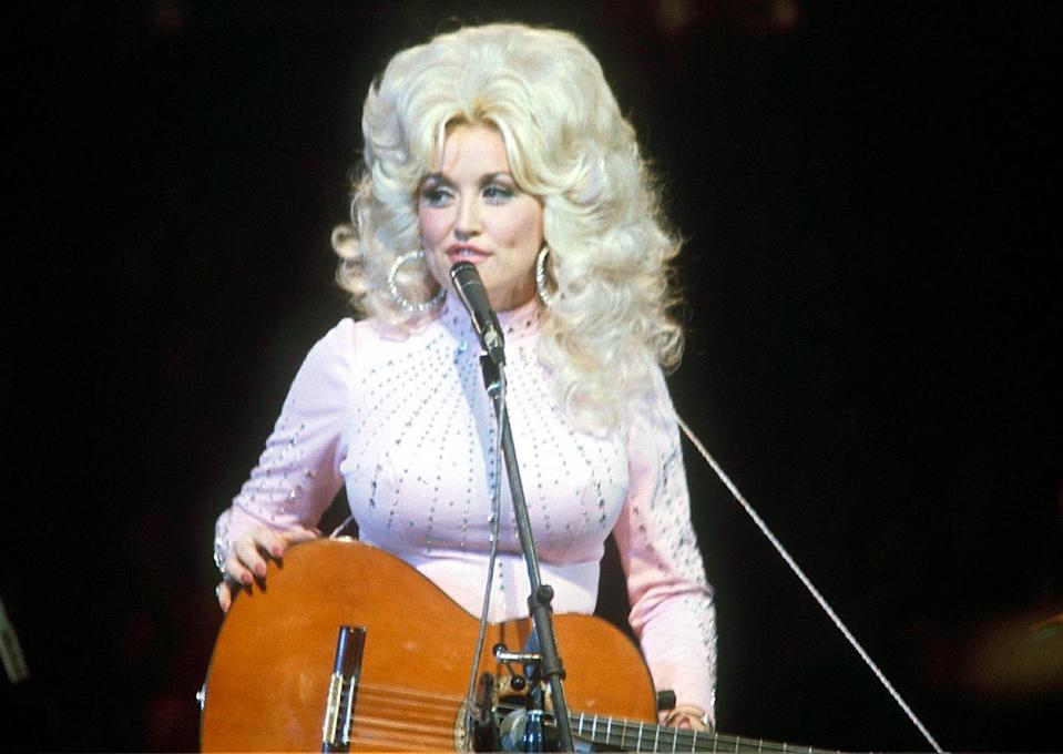 <p>From the start, Parton's style always featured some sort of sparkle, seen here in an embellished high-neck, baby pink look on stage in 1976. </p>