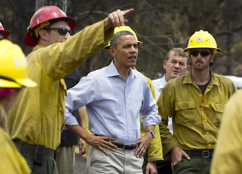 President Barack Obama talks with firefighters as he tours the Mountain Shadow neighborhood devastated by wildfires, Friday, June 29, 2012, in Colorado Springs, Colo. (AP Photo/Carolyn Kaster)