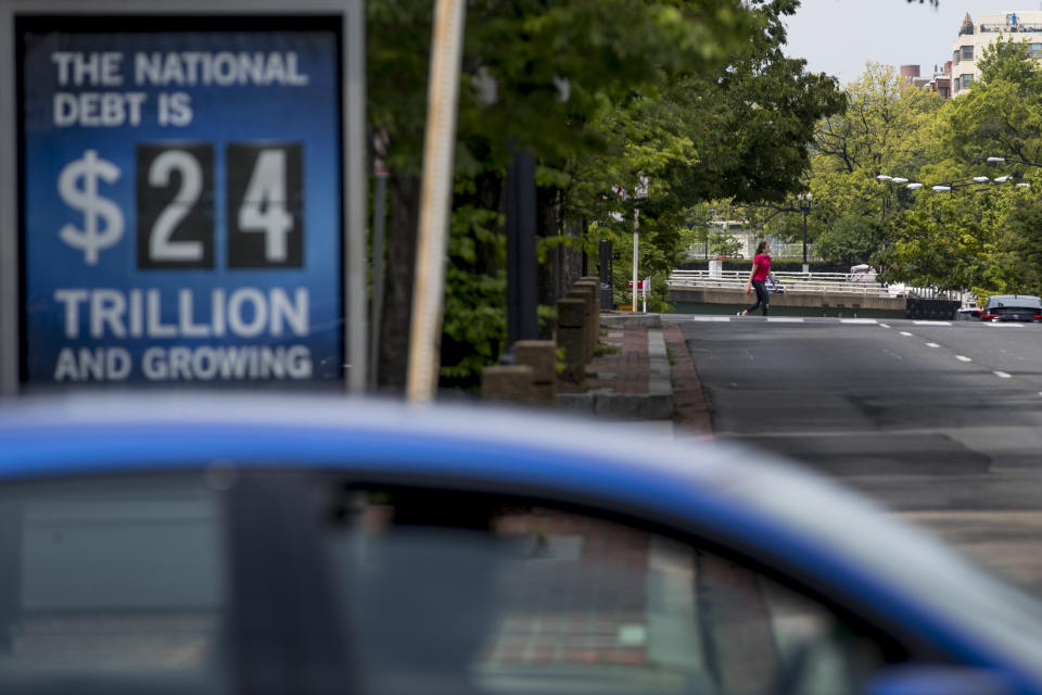A sign displaying the size of the national debt is displayed along an empty K Street, an area usually packed with people this time of day, Wednesday, April 29, 2020, in Washington. (AP Photo/Andrew Harnik)