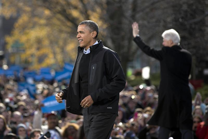 President Barack Obama walks to the podium as former President Bill Clinton waves to the crowd at right during a campaign event in the State Capitol Square, Sunday, Nov. 4, 2012, in Concord, N.H. (AP Photo/Carolyn Kaster)