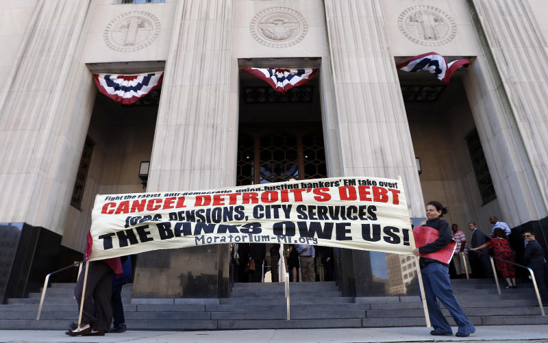 Protesters carry a sign outside the Levin Federal Courthouse in Detroit, Wednesday, July 24, 2013. Detroit's bankruptcy is hitting a courtroom for the first time as a judge considers what to do with challenges from retirees who claim their pensions are protected by the Michigan Constitution.(AP Photo/Paul Sancya)