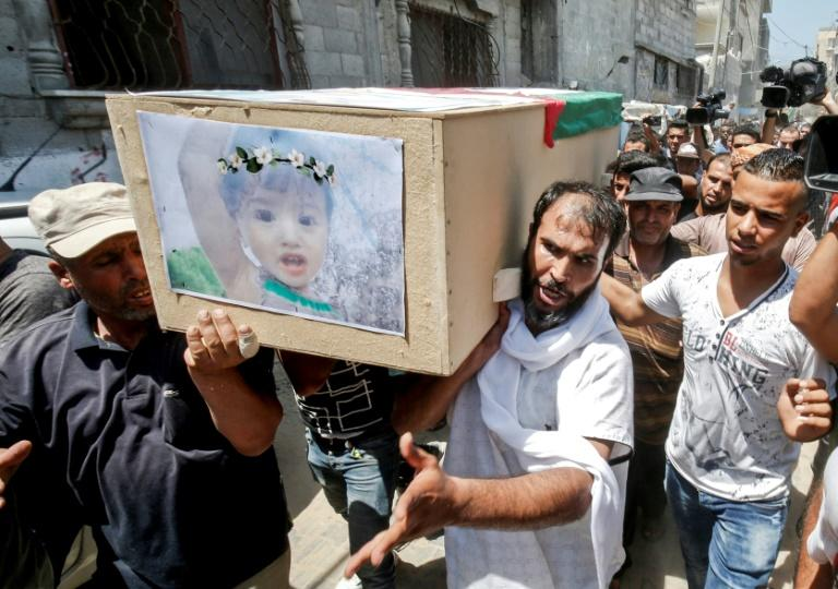 Palestinian mourners carry the coffin of 18-month-old Bayan who was killed with her mother in an Israeli air strike on Gaza