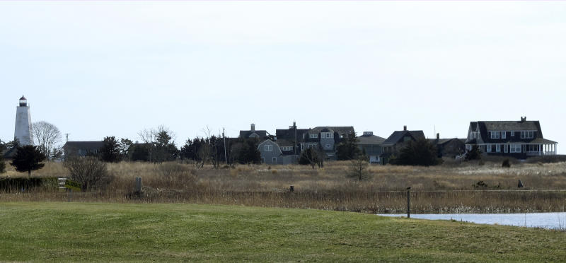 In this April 2, 2019 photo, multimillion-dollar homes and a lighthouse sit on a peninsula in Old Saybrook, Conn. The homes are among more than 900 structures on the East Coast that would become newly eligible for federal disaster aid, under a proposed remapping of coastal protection zones by the U.S. Fish & Wildlife Service. (AP Photo/Dave Collins)