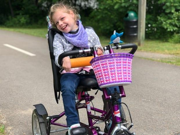 Claire McCloskey, 9, rides an adaptive bike that was fully funded through the Bikes 'n' Trikes program at the Stan Cassidy Centre for Rehabilitation in Fredericton.   (Gary Moore/CBC - image credit)