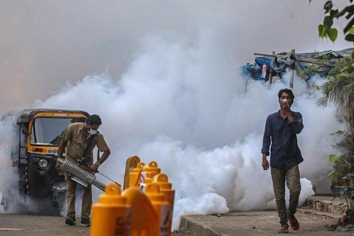 A municipal worker wearing a face mask uses a fumigation spray machine near a vaccination centre in Mumbai, India, 30 April 2021.