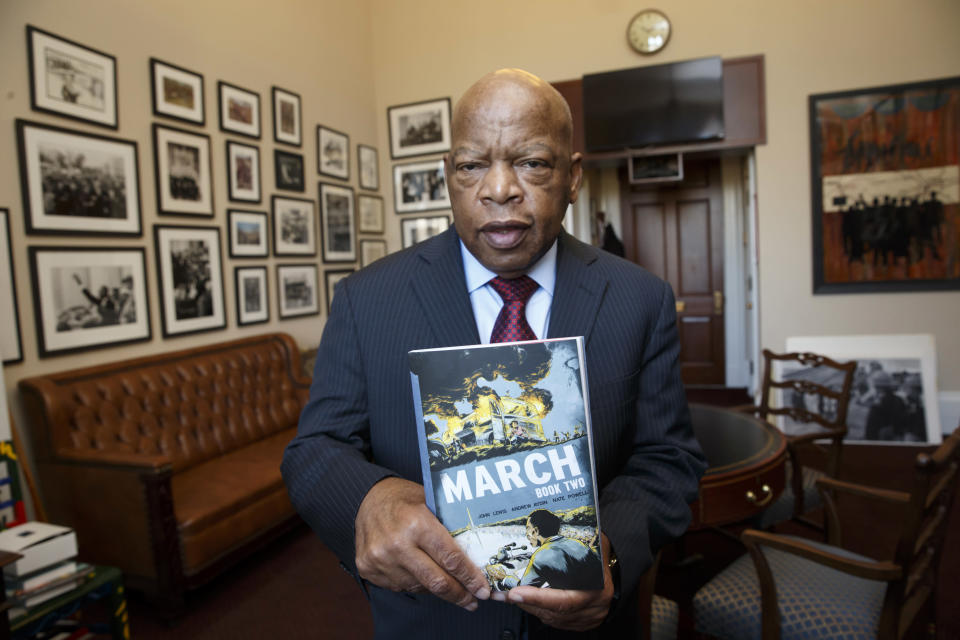 Rep. John Lewis, D-Ga., holds the new installment of his award-winning graphic novel on civil rights and nonviolent protest, on Capitol Hill in Washington on Jan. 15, 2015. A comic book is about Martin Luther King Jr. helped bring John Lewis into the civil rights movement. The longtime Democratic congressman from Georgia now hopes that graphic novels about his life and what his contemporaries endured to overcome racism will guide today's protesters in search of justice. (Photo: J. Scott Applewhite/AP)
