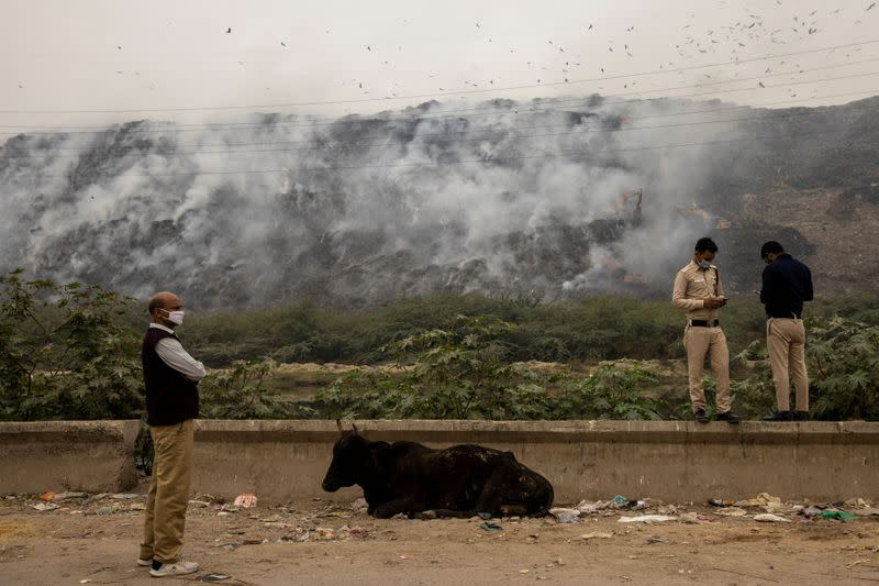 Members of Delhi government anti-pollution squad report the status of the fire as smoke billows from burning garbage at the Ghazipur landfill site in New Delhi