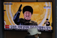 "A man wearing a face mask sits in front of a TV screen showing North Korean leader Kim Jong Un, at the Seoul Railway Station in Seoul, South Korea, Friday, Jan. 15, 2021. The letters read ""Kim Jong Un attended stage in Thursday night's parade celebrating a ruling party congress."" (AP Photo/Lee Jin-man)"