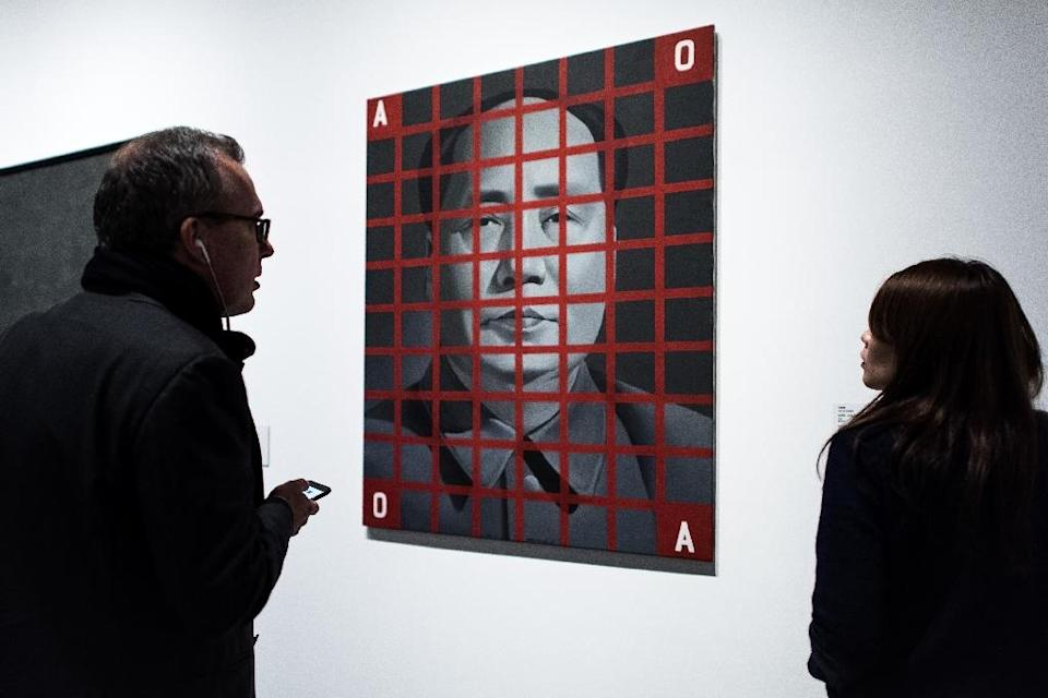 "Visitors stand by an artwork by Chinese artist Wan Guangyi titled ""Mao Zedong: red Grid No. 2"" during the preview of the M+ Sigg art show in Hong Kong (AFP Photo/Philippe Lopez)"