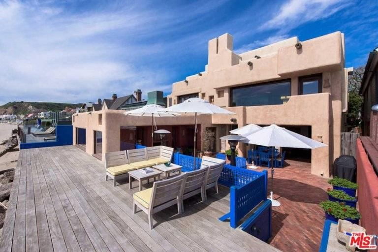 The colorful property includes its own private pool, garden, and gym
