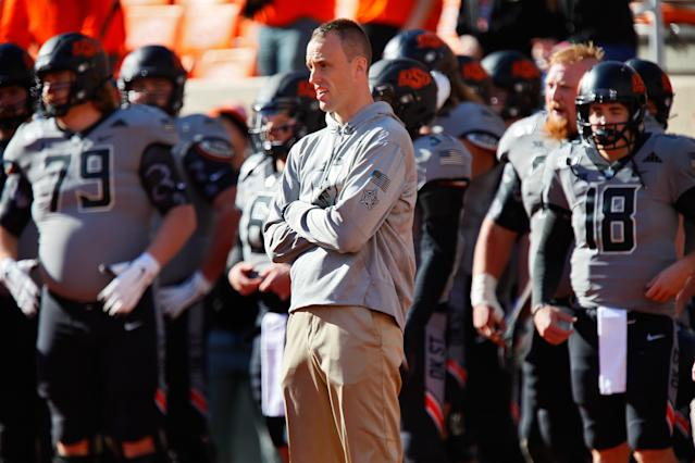"Offensive coordinator Sean Gleeson of the <a class=""link rapid-noclick-resp"" href=""/ncaaf/teams/oklahoma-st/"" data-ylk=""slk:Oklahoma State Cowboys"">Oklahoma State Cowboys</a> watches his team before a game against the <a class=""link rapid-noclick-resp"" href=""/ncaaw/teams/kansas/"" data-ylk=""slk:Kansas Jayhawks"">Kansas Jayhawks</a> on Nov. 16, 2019. (Brian Bahr/Getty Images)"