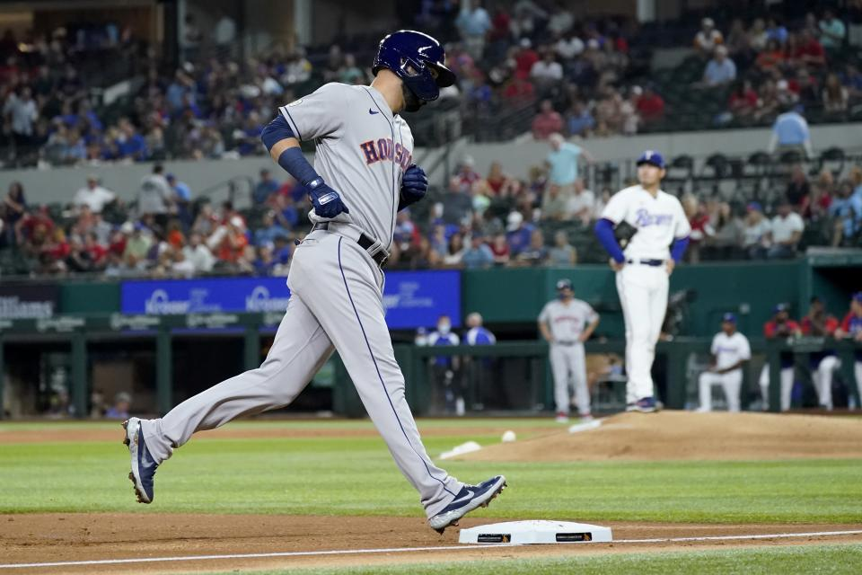 Houston Astros' Marwin Gonzalez rounds the bases after hitting a solo home run off of Texas Rangers starting pitcher Kohei Arihara, rear, in the second inning of a baseball game in Arlington, Texas, Wednesday, Sept. 15, 2021. (AP Photo/Tony Gutierrez)