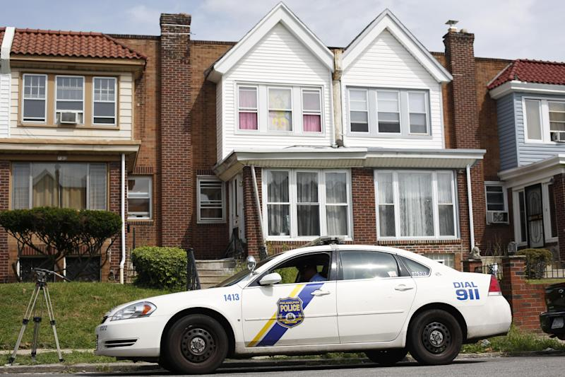 A police officer sits outside the home, center, of a severely disabled 3-year-old girl who was pronounced dead at a nearby hospital, Monday, Sept. 9, 2013, in Philadelphia. Nathalyz Rivera, a twin, weighed just 11 pounds when she died and police in Philadelphia called her death a homicide. (AP Photo/Matt Rourke)