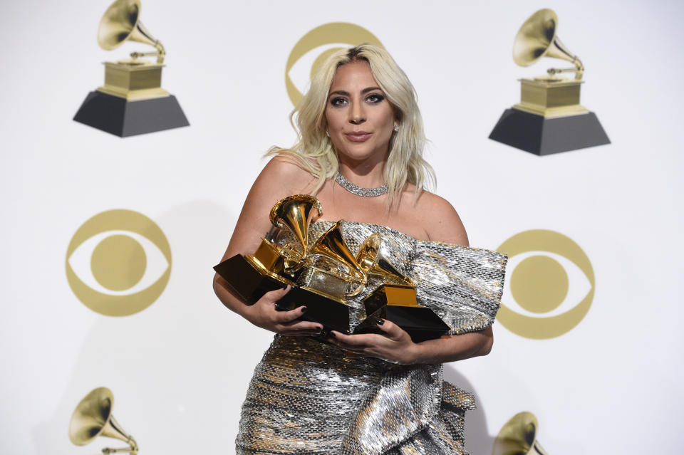 Lady Gaga poses in the press room with her awards for best pop solo performance for