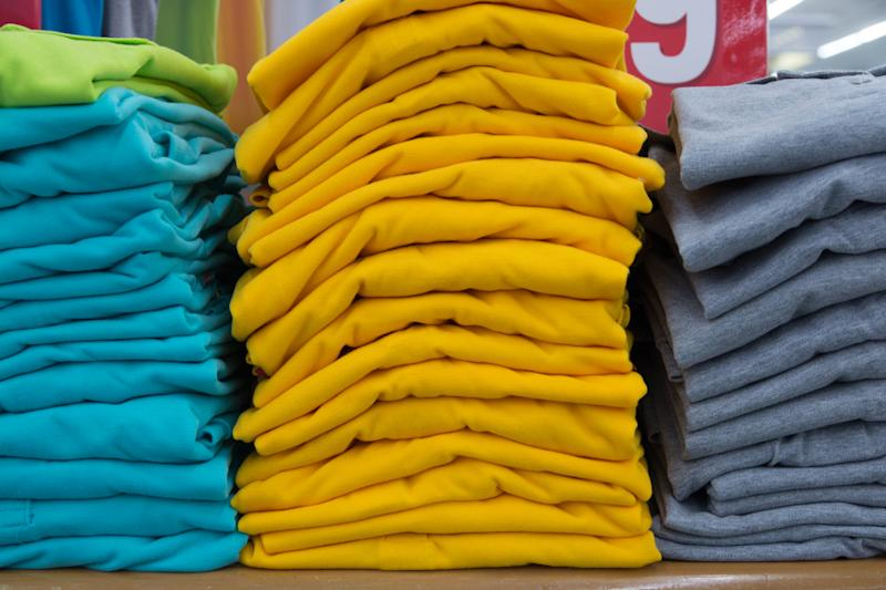 Stack of T-shirt in Department Store or Shopping Mall Retail Store Shop. Yellow, Blur and Grey Color Leisure shirt.