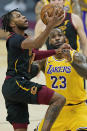 Cleveland Cavaliers' Darius Garland, left, drives to the basket against Los Angeles Lakers' LeBron James in the first half of an NBA basketball game, Monday, Jan. 25, 2021, in Cleveland. (AP Photo/Tony Dejak)