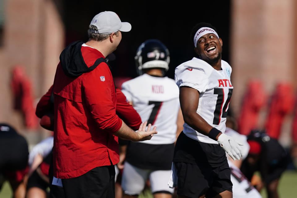 Atlanta Falcons wide receiver Russell Gage (14) laughs as he walks past head coach Arthur Smith during their NFL training camp football practice Sunday, Aug. 1, 2021, in Flowery Branch, Ga. (AP Photo/John Bazemore)