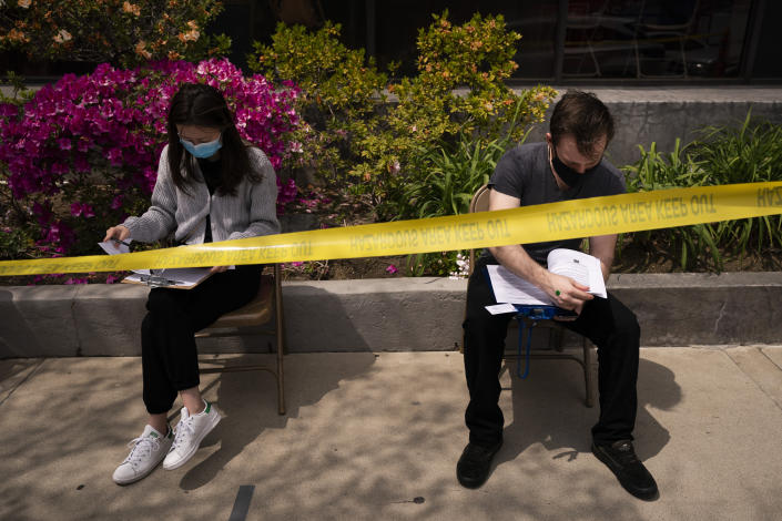 Karl Pajak, 28, right, and Yuting Yu, 22, fill out forms to get the Moderna vaccine at a vaccination center in the Chinatown neighborhood of Los Angeles, Monday, April 12, 2021. The city of Los Angeles has opened up vaccines to younger people, days ahead of the state broadening eligibility to everyone 16 and up. (AP Photo/Jae C. Hong)