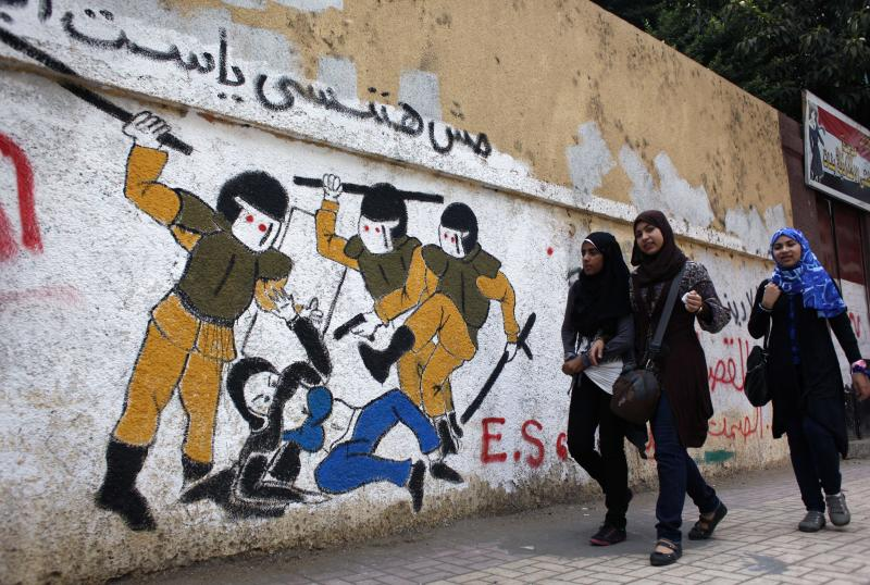 "In this Thursday, Oct. 4, 2012 photo, Egyptian girls walk past a mural inspired by a widely circulated photo of Egyptian police beating and stripping a veiled female protester, on a recently whitewashed wall with Arabic that reads ""we will not forget you our lady,"" in Tahrir Square, Cairo, Egypt. Graffiti has been among the most powerful art forms and tools of Egypt's revolution and the turbulent months since, but it also has proven to be its most vulnerable and ephemeral. So a group of artists, photographers and a publisher joined hands to preserve the images. ""Wall Talk"" _ their newly released, 680-page book _ collects hundreds of photos of graffiti dating from the Jan. 25, 2011 eruption of the revolt against then-President Hosni Mubarak until today. (AP Photo/Nasser Nasser, File)"