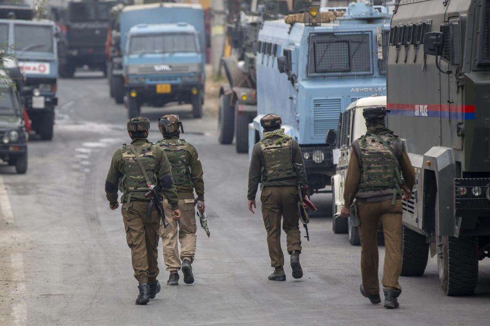 Indian policemen walk towards the site of a gun battle on the outskirts of Srinagar, Indian controlled Kashmir, Sunday, Nov. 1, 2020. According to police, Indian government forces killed Saifullah Mir, a top rebel commander of the region's largest rebel group, Hizbul Mujahideen which has spearheaded an armed rebellion against Indian rule for decades. (AP Photo/ Dar Yasin)