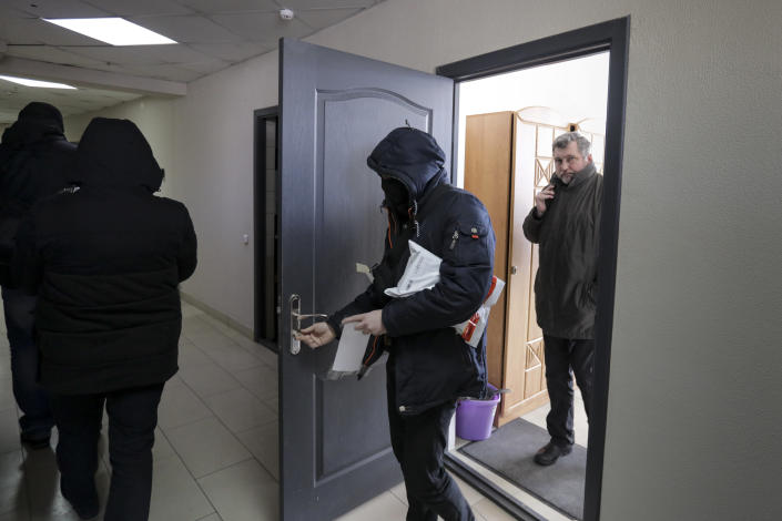 Police carry documents and computers out of the office of the Belarusian Association of Journalists as Andrei Bastunets, the head the Association, right, stands inside the office in Minsk, Belarus, Tuesday, Feb. 16, 2021. Authorities in Belarus have raided the homes and offices of journalists and human rights activists. It is the latest move aimed at squelching a wave of demonstrations against authoritarian President Alexander Lukashenko. Police searched the offices of the Belarusian Association of Journalists and the Viasna human rights center, as well as the apartments of its members. (AP Photo)