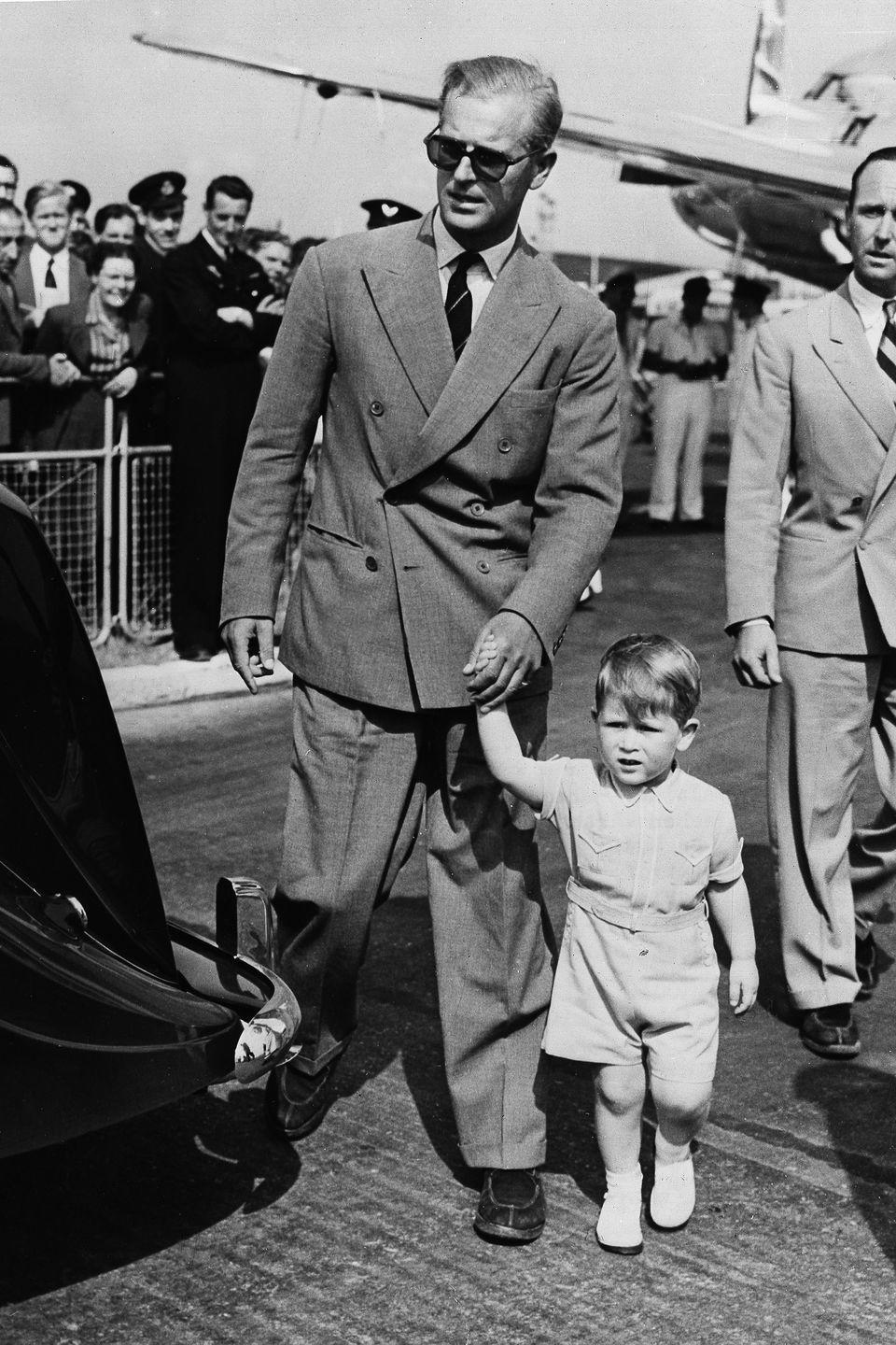 <p>Walking hand-in-hand with his father, Prince Phillip, at the London airport upon the family's return from Malta.</p>