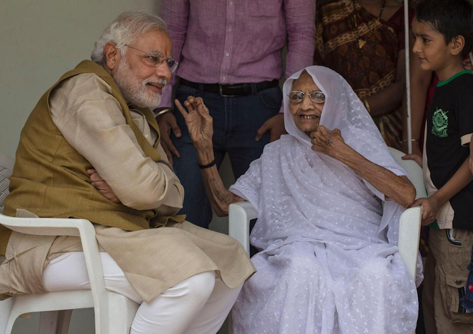<p>File: Indian prime minister Narendra Modi seen with his mother Heeraben Modi after seeking her blessing on 16 May, 2014 in Ahmedabad, India after winning the general election</p> (Getty Images)