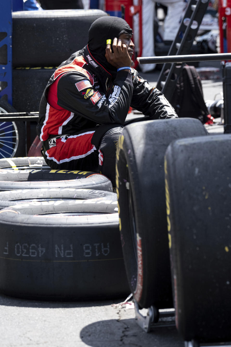 A crew member sits on tires during a NASCAR Xfinity Series auto race at Charlotte Motor Speedway, Saturday, May 29, 2021, in Charlotte, N.C. (AP Photo/Ben Gray)