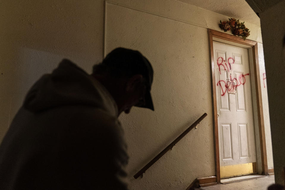 """The message """"RIP Debo"""" is spray painted on the apartment door that had been the home of 41-year-old Debbie Barnette, a mother of three, in Huntington, W.Va., Thursday, March 18, 2021. Barnette, bold and headstrong, had struggled with addiction all her life. She overdosed many times and developed the infections that often follow injection drug use. By the time she sought treatment, the infection in her heart was too far gone to save. Lying in a hospice bed, her sister, Lesa, had to tell her she was dying. Debbie asked her why. """"The drugs got you, babe,"""" Lesa remembers saying. """"They got you."""" The only peace Lesa has is that now she's finally free. (AP Photo/David Goldman)"""