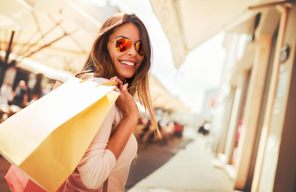 A smiling young woman holds shopping bags.