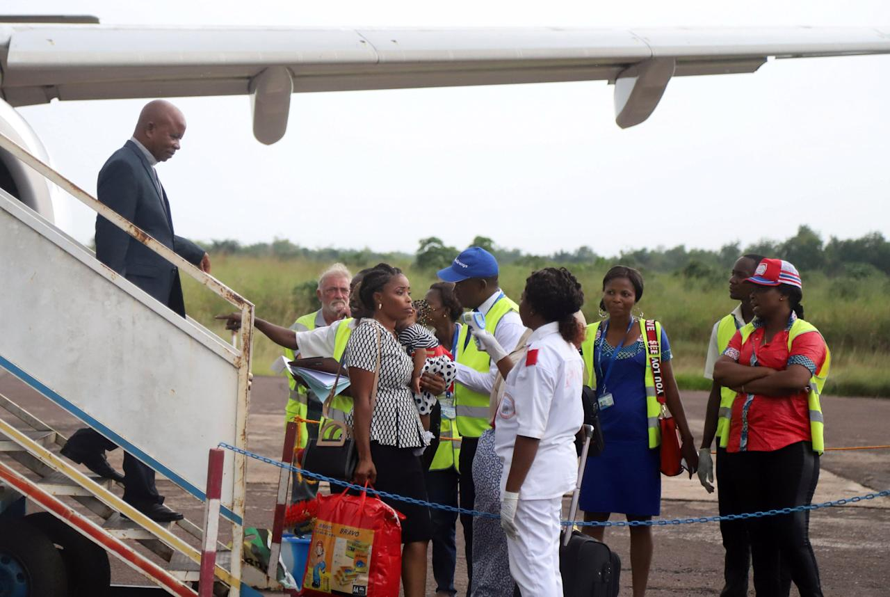 Congolese health workers check the temperature of passengers disembarking from a Congo Airways plane in Mbandaka, Democratic Republic of Congo May 19, 2018. REUTERS/Kenny Katombe