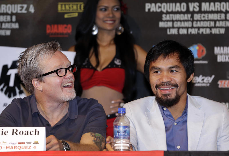 Manny Pacquiao, right, and manager Freddie Roach react to comments during a news conference, Wednesday, Dec. 5, 2012, in Las Vegas. Pacquiao is scheduled to take on Juan Manuel Marquez in a welterweight boxing match on Saturday. (AP Photo/Julie Jacobson)