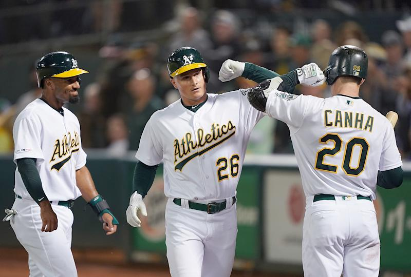 Matt Chapman #26 of the Oakland Athletics is congratulated by Marcus Semien #10 and Mark Canha #20 after Chapman hit a three-run home run against the Los Angeles Angels of Anaheim in the bottom of the third inning at Ring Central Coliseum on September 3, 2019 in Oakland, California. (Photo by Thearon W. Henderson/Getty Images)