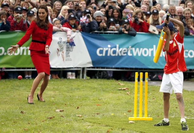 Catherine (L), the Duchess of Cambridge, tries to catch a ball hit by a young boy as she and her husband, Britain's Prince William, attend a promotional event for the upcoming Cricket World Cup in Christchurch April 14, 2014. The Prince and his wife Kate are undertaking a 19-day official visit to New Zealand and Australia with their son George. REUTERS/Phil Noble (NEW ZEALAND - Tags: ROYALS ENTERTAINMENT POLITICS)