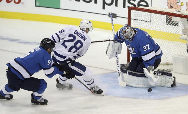 Winnipeg Jets goaltender Connor Hellebuyck (37) stops Toronto Maple Leafs' Connor Brown (28) as he is trailed by Dmitry Kulikov (5) during first period NHL hockey action in Winnipeg, Manitoba, Wednesday, Oct. 24, 2018. (Trevor Hagan/The Canadian Press via AP)