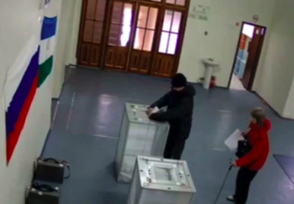 <em>A man allegedly stuffs ballots into a ballot box at a polling station in Tambov during the Russian election (PA)</em>