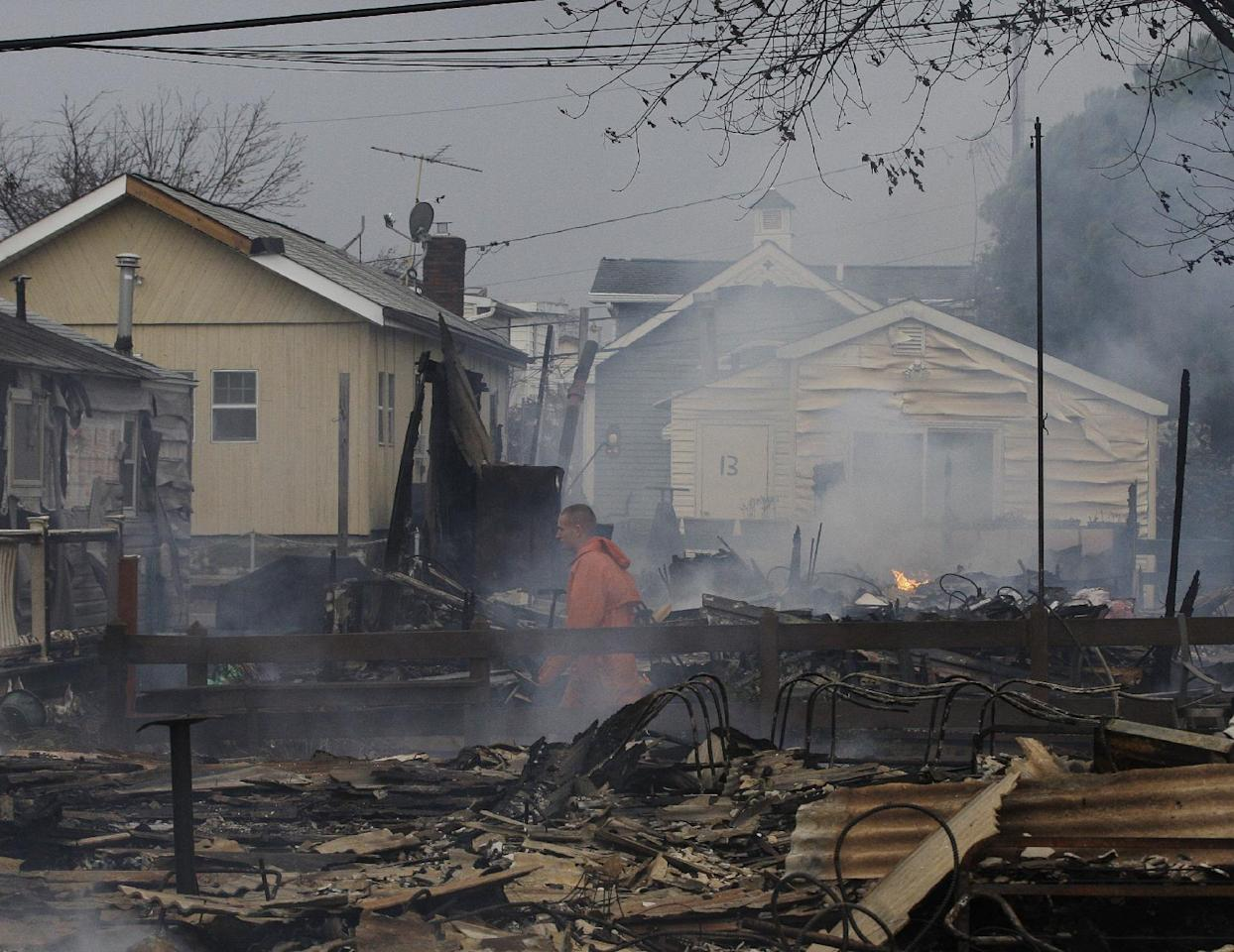 Keith Klein walks through homes damaged by a fire at Breezy Point in the New York City borough of Queens. Tuesday, Oct. 30, 2012. The fire destroyed between 80 and 100 houses Monday night in an area flooded by the superstorm that began sweeping through earlier. (AP Photo/Frank Franklin II)
