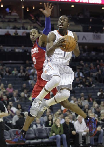 Charlotte Bobcats' Kemba Walker (1) drives past Philadelphia 76ers' Andre Iguodala during the first half of an NBA basketball game in Charlotte, N.C., Monday, Feb. 13, 2012. (AP Photo/Chuck Burton)