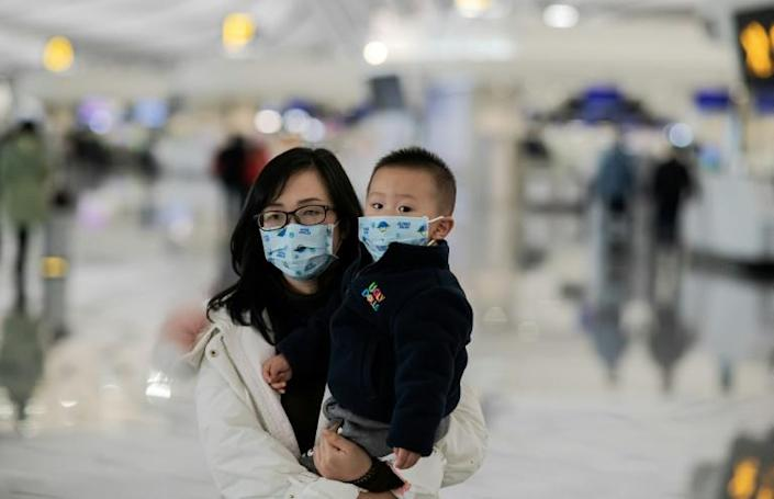 A woman and her child walk toward the check-in counter at Daxing international airport in Beijing (AFP Photo/NICOLAS ASFOURI)