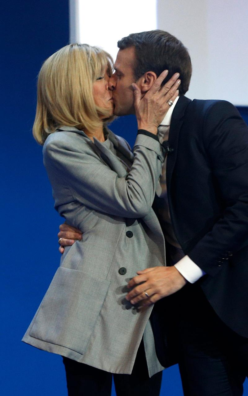 French centrist presidential candidate Emmanuel Macron kisses his wife Brigitte before addressing his supporters at his election day headquarters in Paris - Credit: AP