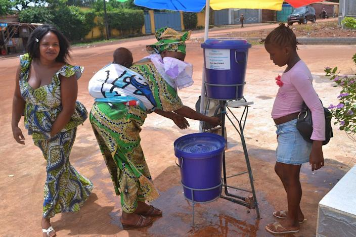 Guinean women wash their hands at the entrance of the Sino-Guinean hospital of Kipe on June 25, 2014 (AFP Photo/Cellou Binani)