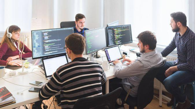 Group of software developers sitting at desktop computers being focused on their work.
