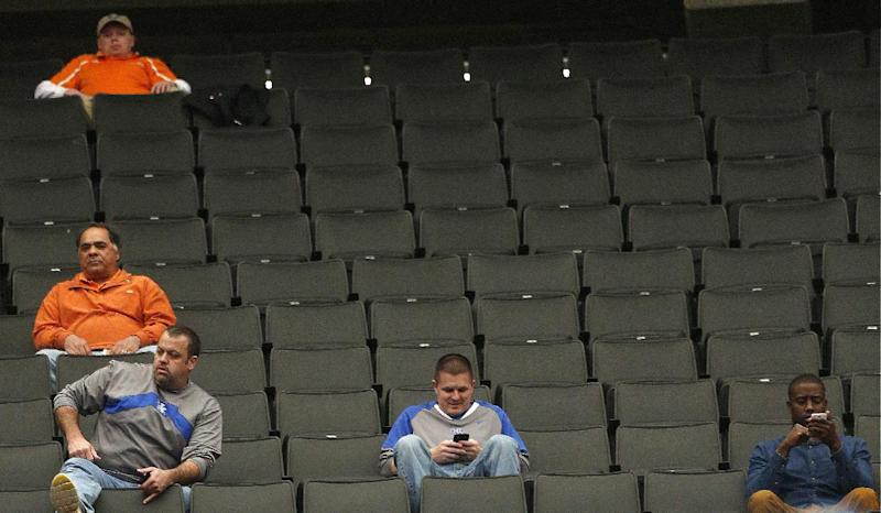 People sit in the stands during the first half of an NCAA college basketball game in the quarterfinal round of the Southeastern Conference tournament, Friday, March 14, 2014, in Atlanta. (AP Photo/John Bazemore)