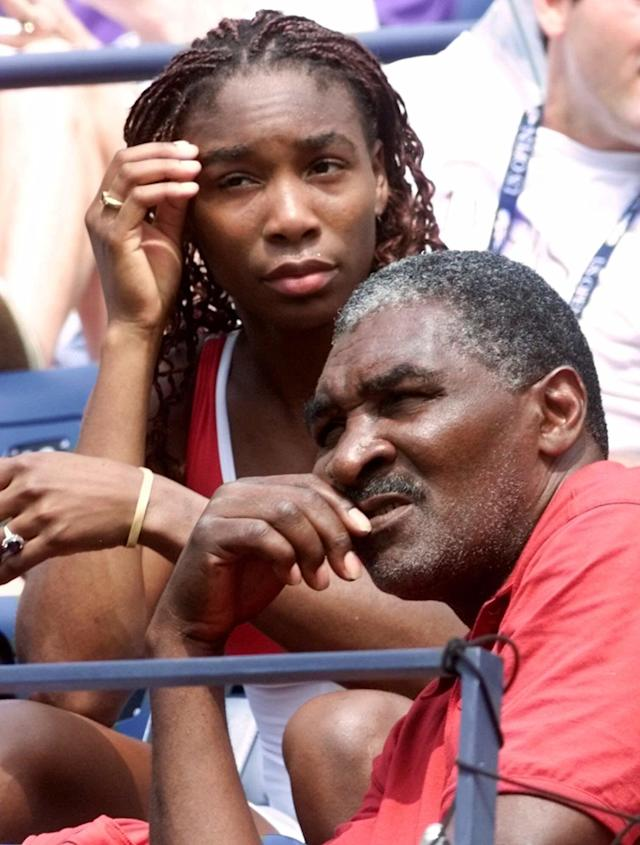 """FILE - In this Sept. 4, 2000, file photo, Venus Williams watches her sister Serena play Australia's Jelena Dokic alongside her father and coach Richard Williams at the U.S. Open tennis tournament in New York. His new book, """"Black and White: The Way I See It,"""" comes out May 6. It goes into detail about how Indian Wells, as he writes, """"disgraced America."""" (AP Photo/Suzanne Plunkett, File)"""
