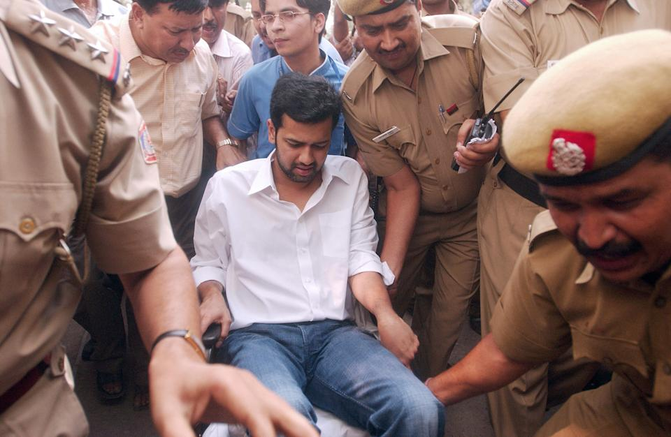 New Delhi, INDIA:  Rahul Mahajan, son of the late Indian Hindu nationalist leader Pramod Mahajan killed in May by his brother, is surrounded by policemen as he arrives on a wheelchair at the Patiala House Court in New Delhi, 06 June 2006.  Mahajan was earlier discharged from the Apollo Hospital and brought to a police station where a case has been registered against him under the Narcotic Drugs and Psychotropic Substances Act, after being arrested 05 June. Mahajan had been on life support after a late-night drinking binge that also left the family secretary dead.              AFP PHOTO/ Manpreet ROMANA  (Photo credit should read MANPREET ROMANA/AFP via Getty Images)