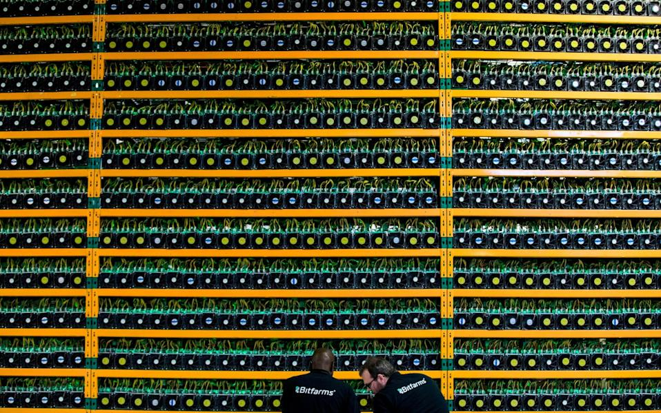 Two technicians inspect bitcon mining at Bitfarms in Saint Hyacinthe, Quebec - LARS HAGBERG/AFP/Getty Images
